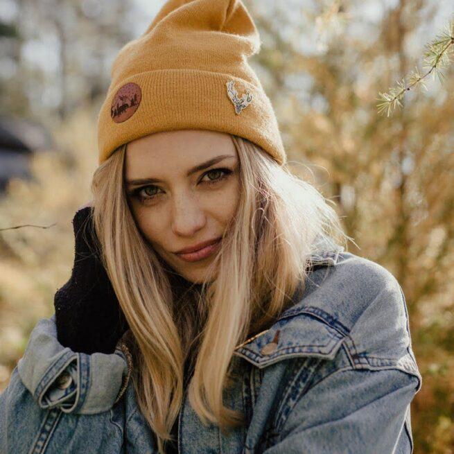Przypinka z leśnej serii Jeleń duch lasu z kawiatami między porożem wpiety w żółta czapkę dziewczyny o blond włosach od Polskiego producenta emaliowanych przypinek