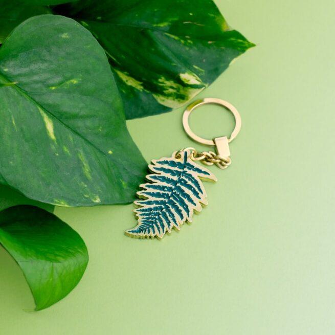 Ręcznie emaliowany brelok do kluczy, do torebki w kształcie liścia paproci w tle kwiat doniczkowy od producenta metalowych breloczków i pinów opd Pinswear