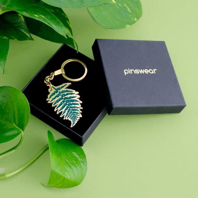 Ręcznie emaliowany brelok do kluczy, do torebki w kształcie liścia paproci w czarnym pudełku od producenta metalowych breloczków i pinów opd Pinswear