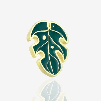 Przypinki metalowe emaliowane od producenta pinów Pinswear liść monstery w złotym wykończeniu na różowym tle, kredki w tle