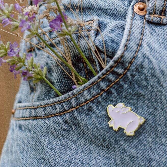 Metalowa przypinka różowego prosiaczka w złotym wykończeniu od producenta Pinswear