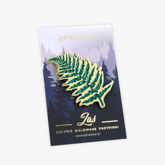 Piny na zamówienie Paproć z serii las wpięty w golf kremowego swetra piegowatej młodej dziewczyny od producenta ręcznie emaliowanych pinów Pinswear