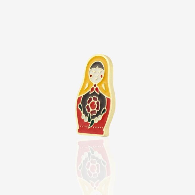 Przypinak ręcznie emaliowana Matrioszka babuszka wpieta na czarną karteczke z kolorowymi budynkami na zamówienie od Polskiego producenta metalowych przypinek Pinswear