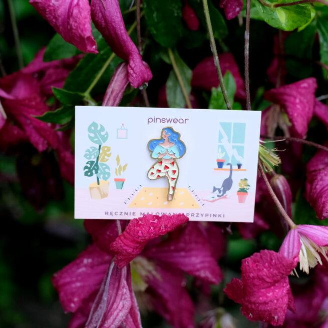 """Metalowe przypinki dziewczyna ćwicząca jogę w pozycji """"Vrksasana"""" od producenta ręcznie emaliowanych pinów od Pinswear w tle różowe róże"""