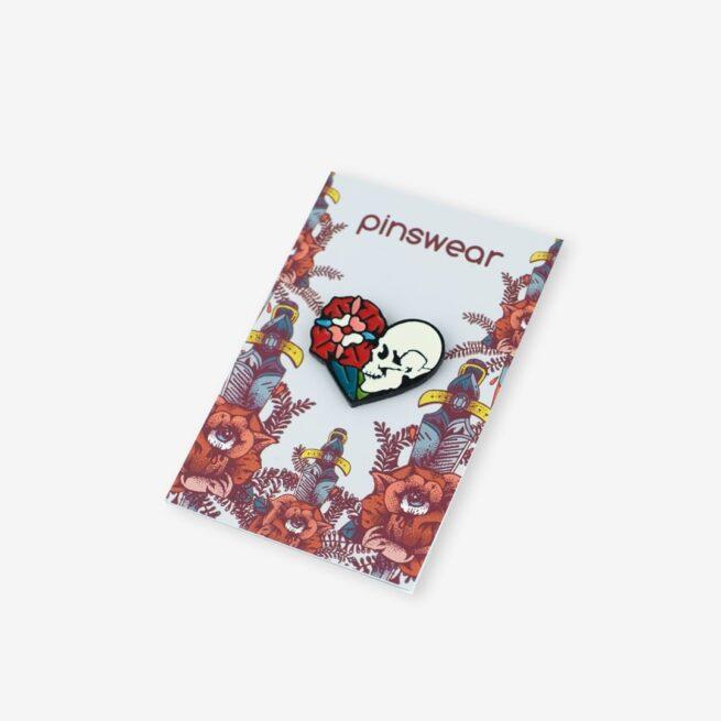 Ręcznie malowana przypinka w kształcie serca w środku retro czaszka z kwiatem wpięta w karteczkę od producenta ręcznie malowanych pinów od Pinswear