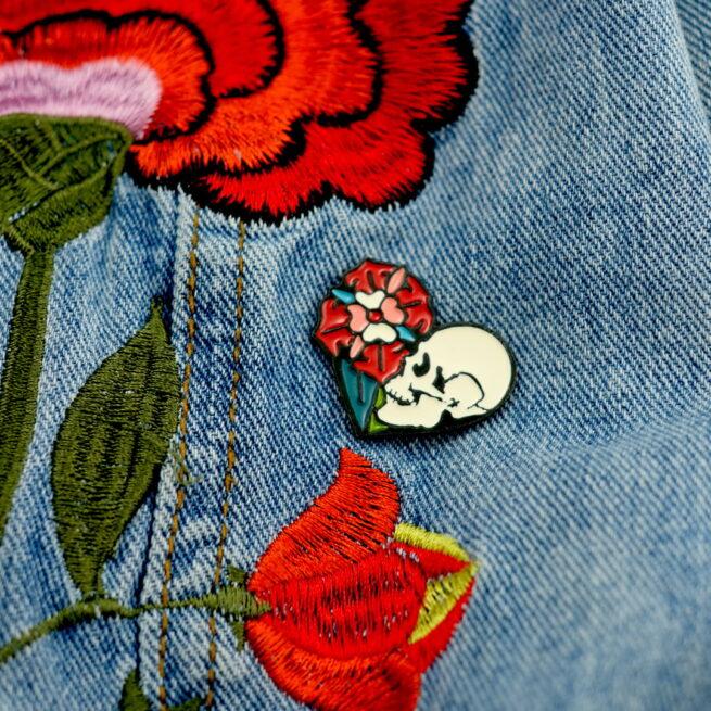 Ręcznie malowana przypinka w kształcie serca w środku retro czaszka z kwiatem wpięta w jeansową kurtkę od producenta ręcznie malowanych pinów od Pinswear