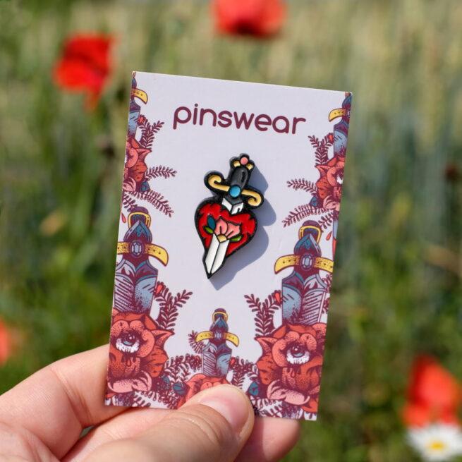 Przypinka z serii miłosnych pinów dla zakochanych na walentynki retro serce przebite sztyletem wpiete do karteczki od producenta pinów ręcznie malowanych od Pinswear w tle łaka z makami polnymi