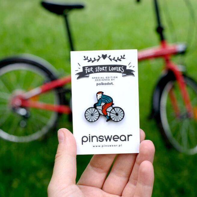 Pinsy od Polskiego producenta recznie malowanych przypinek Pinswear zaprojektowane przez studio graficzne Polkadot rowerzysta Leon patrzący za siebie wpiety w szary plecak w tle szprychy czerwonego roweru