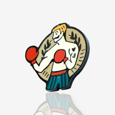 Przypinki z wytatuowanym bokserem z wąsem w szortach na tle tarczy zaprojektowane przez studio graficzne Polkadot wyprodukowane przez producenta ręcznie emaliowanych pinów od Pinswear
