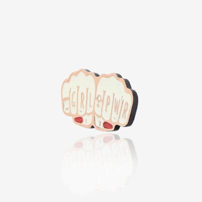 Ręcznie malowana przypinka w kształcie pięści dłoni z napisem girl power wpieta w karteczkę położone na jeansowej kurtce od producenta ręcznie malowanych pinów od Pinswear