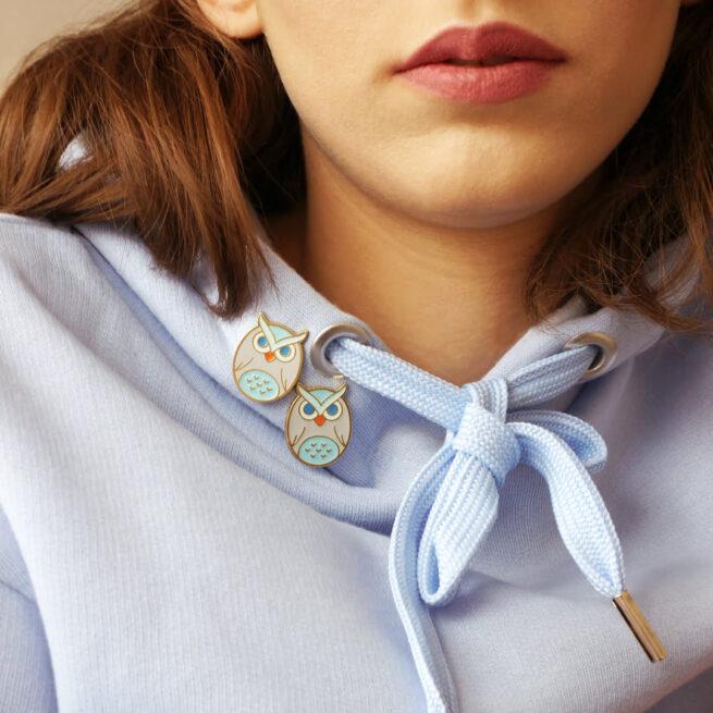 Metalowe przypinki w kształcie sowy w pastelowych kolorach wpiete w liliową bluze brunetki od producenta ręcznie malowanych pinow od Pinswear