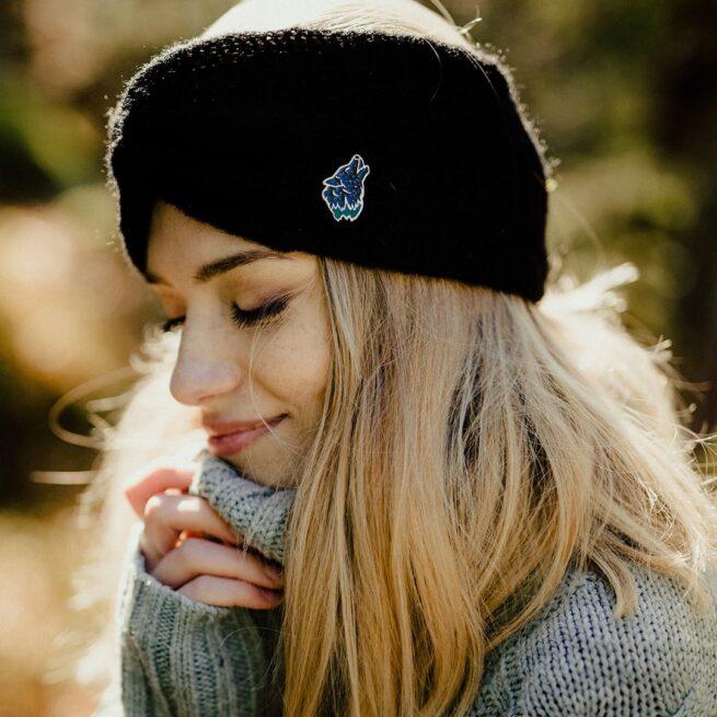 Ręcznie malowane przypinki z serii las głowa wyjącego wilka do księżyca wpięta w czarną opaskę na głowie dziewczyny o blond włosach od producenta pinów metalowych od Pinswear