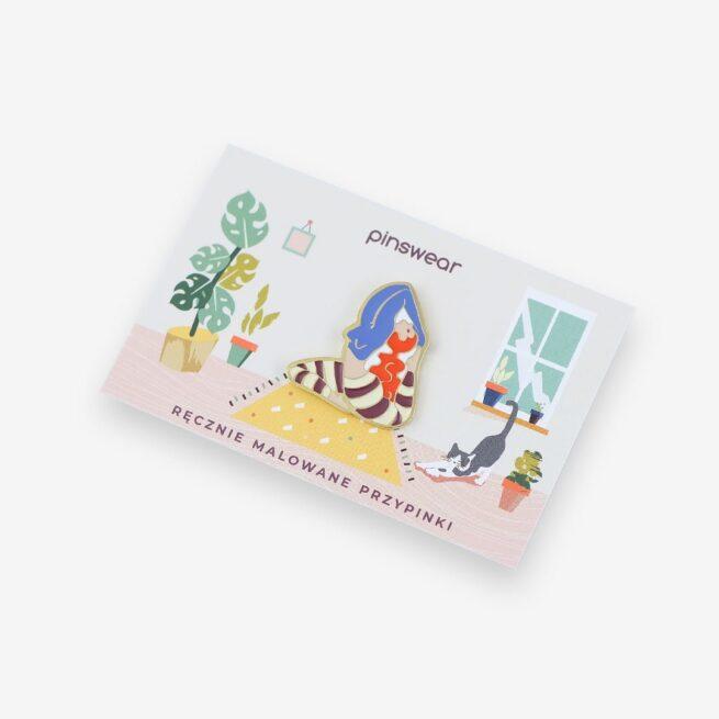 """Metalowe przypinki ruda dziewczyna ćwicząca jogę w pozycji """"Rajakapotasana"""" wpięta w karteczkę od producenta ręcznie emaliowanych pinów od Pinswear"""