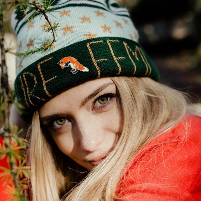 Przypinka rudy Lis Leśny Łowca podczas skoku wpiety w czapkę blondynki z piwnymi oczami od Pinswear producenta ręcznie malowanych pinów od PInswear