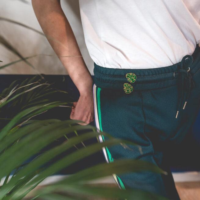 Przypinki metalowe emaliowane od producenta pinów Pinswear liść monstery w złotym wykończeniu wpieta w zielone dresy dziewczyny