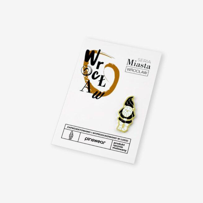 Ręcznie malowana przypinka w kształcie wrocławskiego krasnala w złotym wykończeniu wpięty w karteczkę od Pinswear producenta metalowych pinów