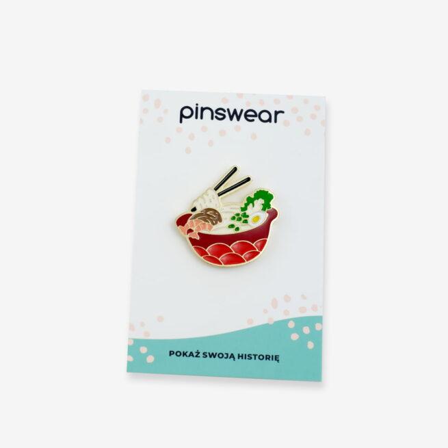 Ręcznie malowany pin kultowa zupa azjatycja ramen z jajkiem, czaszu i krewetkami w czerwonej dekoracyjnej misce, przypinka wpięta w karteczkę od producenta metalowych pinów od Pinswear