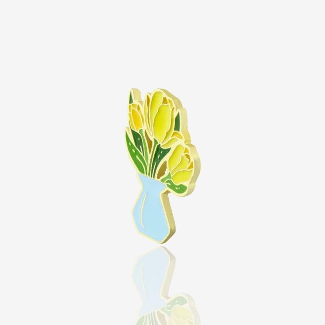Ręcznie malowane metalowe piny w kształcie żółtych tulipanów w niebieskim wazonie wyprudokowane w Polsce od producenta metalowych pinów od Pinswear