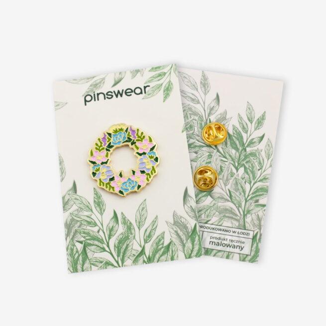 Ręcznie malowane piny w złotym wykończeniu w kształcie kwiatowego wianka od producenta metalowych pinów od pinswear wpięte w karteczkę