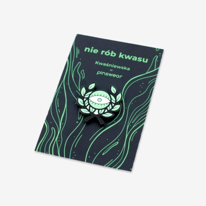 """Ręcznie malowany pin z kolekcji """"nie rób kwasu"""" w kszałcie oka z liśćmi zaprojektowany przez Katarzynę Kwaśniewską dla producenta metalowych pinów dla Pinswear wpiety w personalizowaną karteczkę"""
