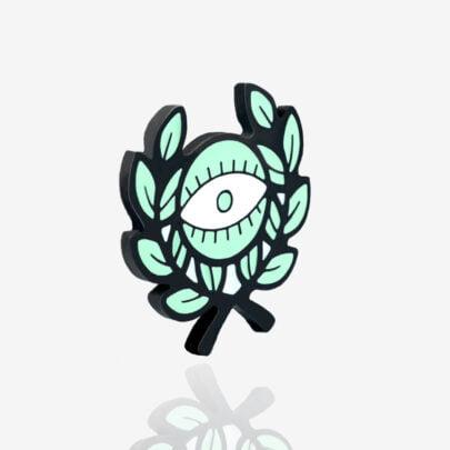 """Ręcznie malowany pin z kolekcji """"nie rób kwasu"""" w kszałcie oka z liśćmi zaprojektowany przez Katarzynę Kwaśniewską dla producenta metalowych pinów dla Pinswear"""