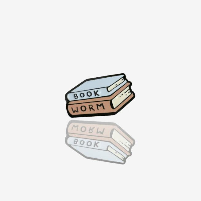 Ręcznie malowany pin ksiązki napisem book worm wykończone w czarnym patynolu od producenta metalowych pinów od Pinswear