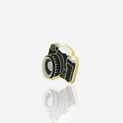 Ręcznie malowany pin aparat lustrzanka od producenta metalowych pinów od Pinswear w kolorze czrno białym wykończony na złoto