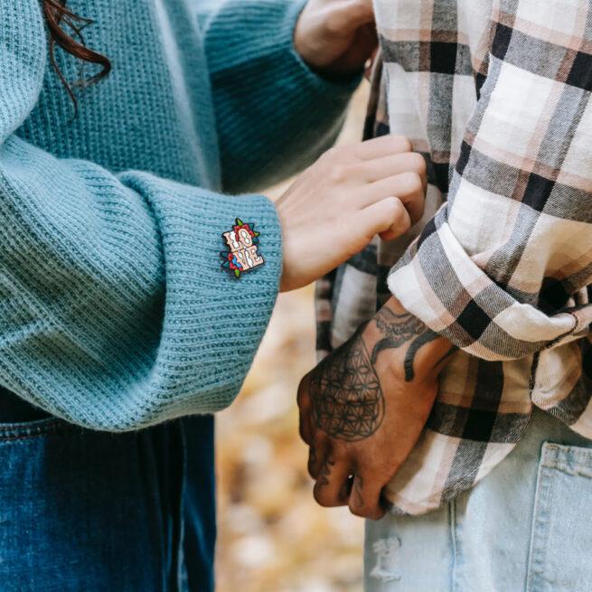 Ręcznie malowany pin w czarnym patynolu napis love w kwiatach kolekcja walentynkowa od producenta metalowych pinow od Pinswear